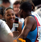 Marion Jones interviews husband Tim Montgomery after second round of 100 meters in the IAAF World Championships in Athletics at Stade de France on Sunday, Aug, 24, 2003.