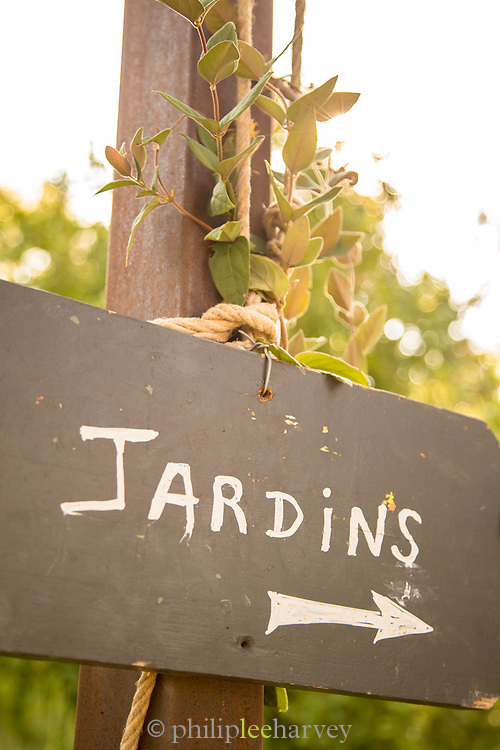 Handwritten in French language sign tied up to metal post showing direction to gardens, Grasse, France