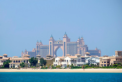 Luxury villas on frond of Palm Island man-made island with Atlantis The Palm hotel to rear in Dubai United Arab Emirates