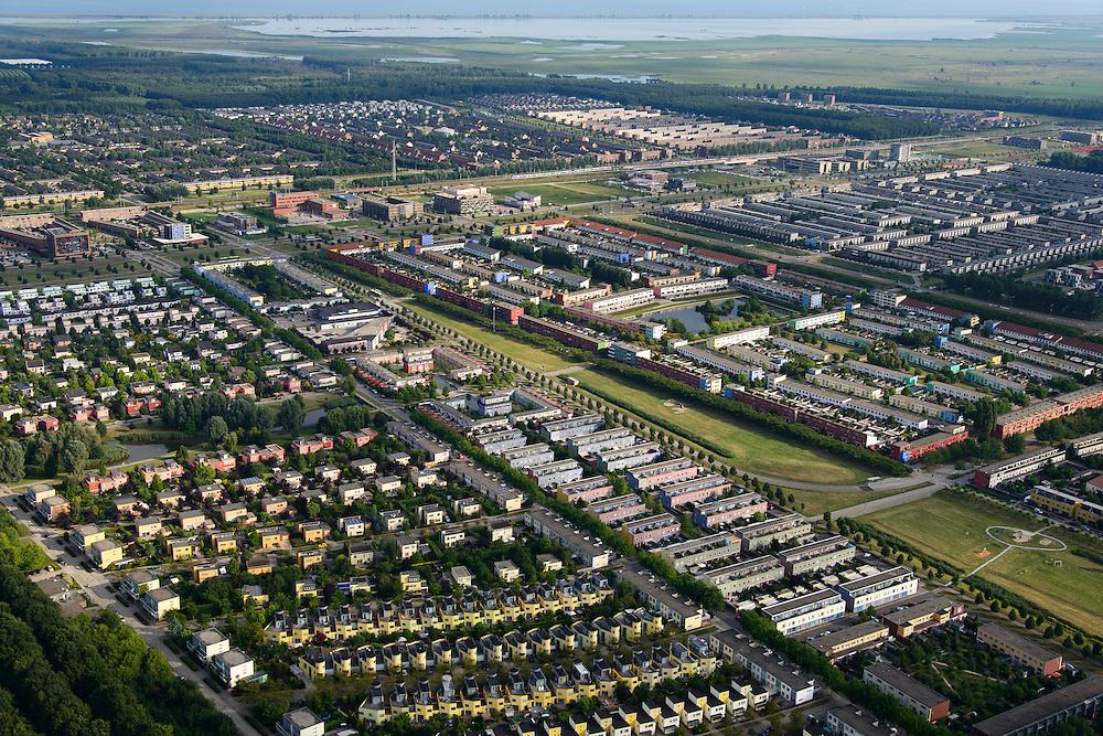 Nederland, Flevoland, Almere, 27-08-2013; Almere-Buiten. Regenboogbuurt met rijen vrolijk gekleurde eengezinswoningen in de voorgrond, Oostvaardersplassen in de achtergrond.<br /> Residential distict Regenbouwbuurt (Rainbow Area),  rows of brightly colored family houses, bird sanctuary Oostvaardersplassen in the back.<br /> luchtfoto (toeslag op standaard tarieven);<br /> aerial photo (additional fee required);<br /> copyright foto/photo Siebe Swart.