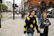 Young woman wearing a jumper coevered in smiley faces in the shopping district of Oxford Street, some wearing face masks and others not on 26th May 2021 in London, United Kingdom. As the coronavirus lockdown continues its process of easing restrictions, more and more people are coming to the West End as more retail businesses open.