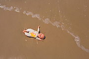 Child abuse concept an abandoned doll in the ebb and flow on an otherwise empty beach
