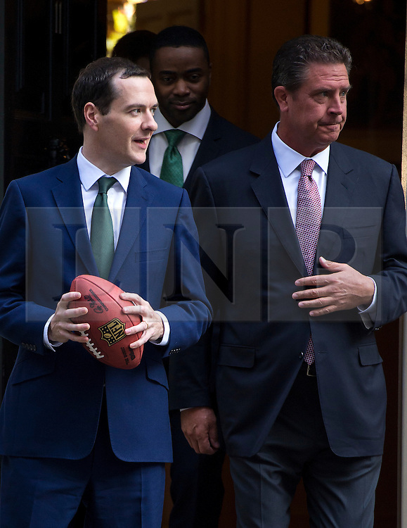 © Licensed to London News Pictures. 02/10/2015. London, UK. British chancellor GEORGE OSBORNE (left) throwing an american football with CURTIS MARTIN (centre) and DAN MARNO (right) after meeting with NFL team owners, execs and former stars at Downing Street ahead of this weekend NFL game at Wembley stadium.  Photo credit: Ben Cawthra/LNP