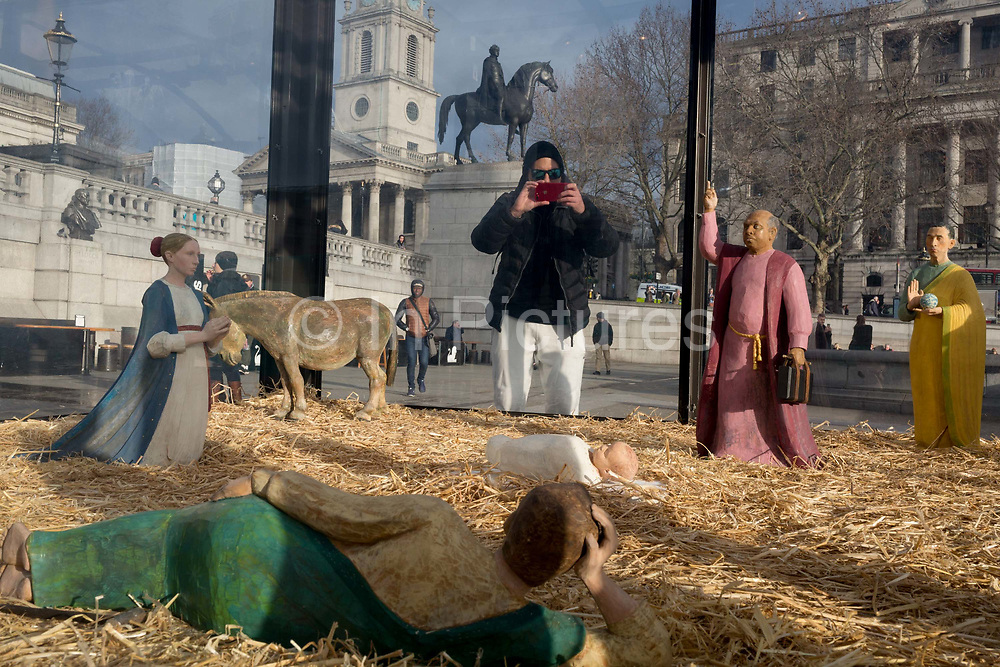 The annual Christmas nativity scene entitled Christmas Crib by the artist Tomoaki Suzuki and located in Trafalgar Square, attracts interest from onlookers, on 13th December 2019, in London, England.