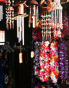 Wind chimes and floral garlands hang for sale in a store in Kapa'a, Kauai'i, Hawai'i