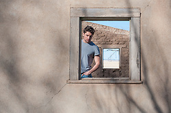 man in an old Adobe home looking through the window