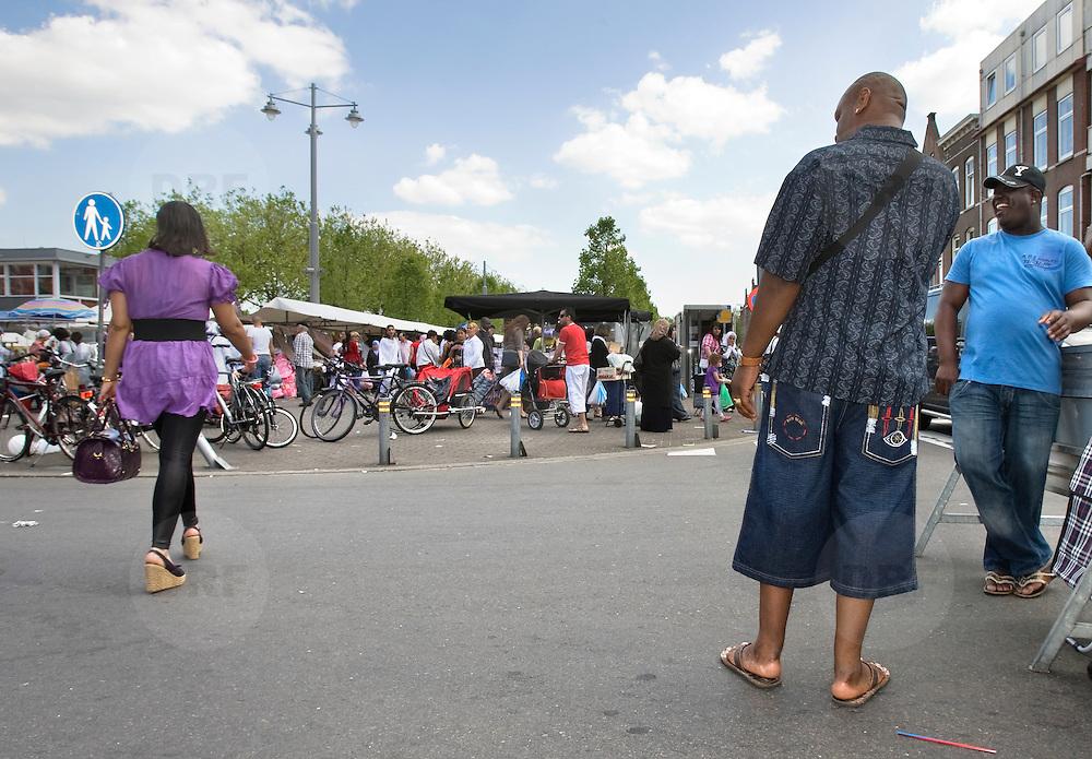 Nederland Rotterdam 30-05-2009 20090530 Foto: David Rozing ..Afrikaanderbuurt, markt Afrikaanderplein Mannen bekijken mooie dame die hen passeert Men checking out lookin at  lady..Foto: David Rozing