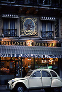 A white, convertible 2CV car is parked outside a boulanger and patisserie, 10th May 1980, Paris, France.