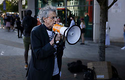 © Licensed to London News Pictures. 31/05/2021. London, UK. Anti-vaccine activist Piers Corbyn speks through a megaphone to people queueing up outside England's biggest vaccine centre at Twickenham Stadium in south west London after the centre said they will vaccinate anyone over the age of 18 today up to 7:30pm. . Photo credit: Peter Macdiarmid/LNP