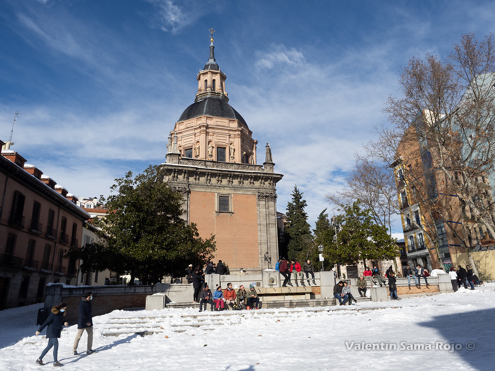 Madrid, Spain. 10th January, 2021. People sitting in the sun at 'Plaza de Carros' in Madrid's downtown, the day after storm Filomena hitted Madrid. After Storm Filomena, Madrid (Spain) is covered in snow and ice, lots of trees have fallen and it is not possible to use the car in most of the streets but people walk around the city. © Valentin Sama-Rojo.