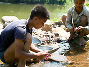 Local boatmen/fishermen Savath and Sengkham prepare fish for cooking over an open fire which they have just caught by electric fishing in a small stream which flows into the Nam Ou river, Phongsaly province, Lao PDR. The Nam Ou river connects small riverside villages and provides the rural population with food for fishing. But this river and others like it, that are the lifeline of rural communities and local economies are being blocked, diverted and decimated by dams. The Lao government hopes to transform the country into 'the battery of Southeast Asia' by exporting the power to Thailand and Vietnam.