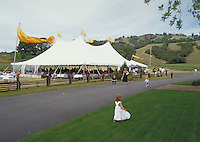 Girl on lawn near tent at winery festival near Philo in Anderson Valley, California