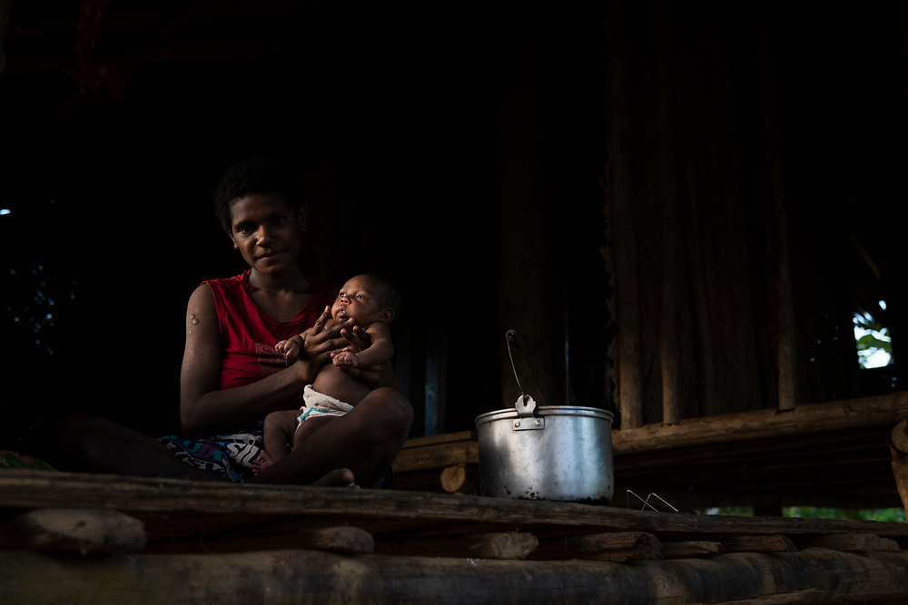 Ageles Sopam holds her baby, illuminated by light from the setting sun, inside their home in Likan, East Sepik Province, Papua New Guinea.<br /><br />(June 20, 2019)