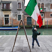 VENICE, ITALY - MARCH 16: A boy plays with an Italian national flag that is displayed ahead of the celebrations for the 150th anniversary of Italy's unification on March 16, 2011 in Venice, Italy. March 17th has been declared National Festivity and events to celebrate the 150th anniversary will run in several Italian cities until the end of the year.