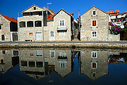 Three houses and reflections in canal, village of Vrboska, island of Hvar, Croatia