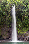 The waterfall at Bombaim, Sao Tome. Sao Tome and Principe, are two islands of volcanic origin lying off the coast of Africa. Settled by Portuguese convicts in the late 1400s and later a centre for slaving, their independence movement culminated in a peaceful transition to self government from Portugal in 1975.