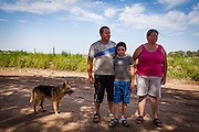 2014/11/18 - Monte Maiz, Argentina: Claúdio Fuentes (34) and Antónia Alaris (36) with their son Axel David Fuentes (8) in front of the soy field that faces their home in Monte Maiz. Their daughter, Antonella Fuentes, was diagnosed with osteosarcoma, a cancerous bone tumor, at the age of 6. She died a few months later.  The cases of cancer grew exponentially in the area since the introduction of glyphosate on the soy cultivation.  707 <br /> Cancer cases per 100,000 pepople were register by health researchers in the core area of soybean cultivation. These are three times as many  as the national average. (Eduardo Leal)