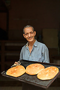 Smiling baker holding tray with fresh bread in bakery, Casablanca, Morocco