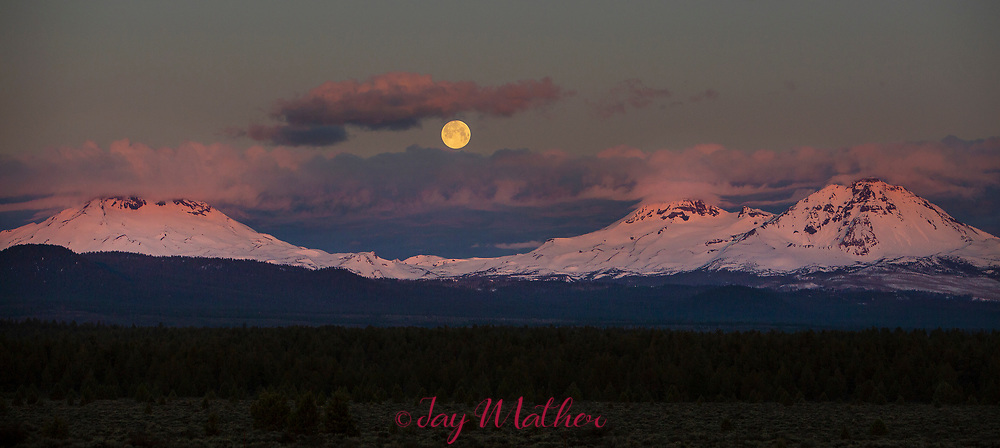 "Full moonset over the Three Sisters. The ""pink moon,"" first full moon of April 2019.<br /> April 19, 2019"