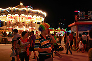 A man wearing a clown wig walks through the carnival grounds of the Qingdao (Tsingtao) Beer Festival in Qingdao, China on 27 August, 2011. Named after the locally brewed Tsingtao Beer, one of China's most famous exports, the festival has grown from a local binge drinking feast to an internationally known festival.