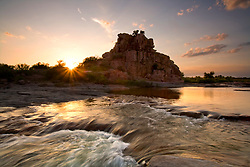 Stock photo of the sun setting behind Eagle Rock along the Llano River in the Texas Hill Country