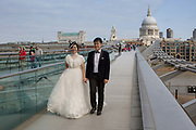 An Asian newlywed couple pose for a morning photoshoot on Millennium Bridge, with St Paul's Cathedral in the background, on the 27th August 2018 in Central London in the United Kingdom.