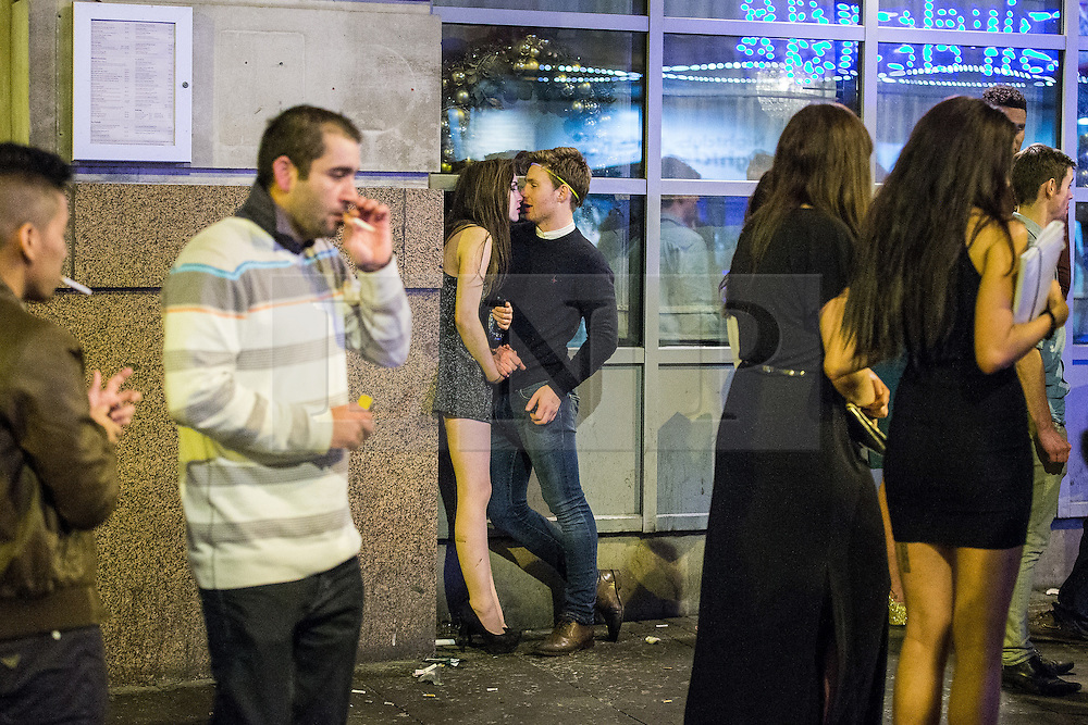 © Licensed to London News Pictures . 01/01/2015 . Manchester , UK . A couple kiss on Withy Grove . Revellers usher in the New Year on a night out in Manchester City Centre .  Photo credit : Joel Goodman/LNP