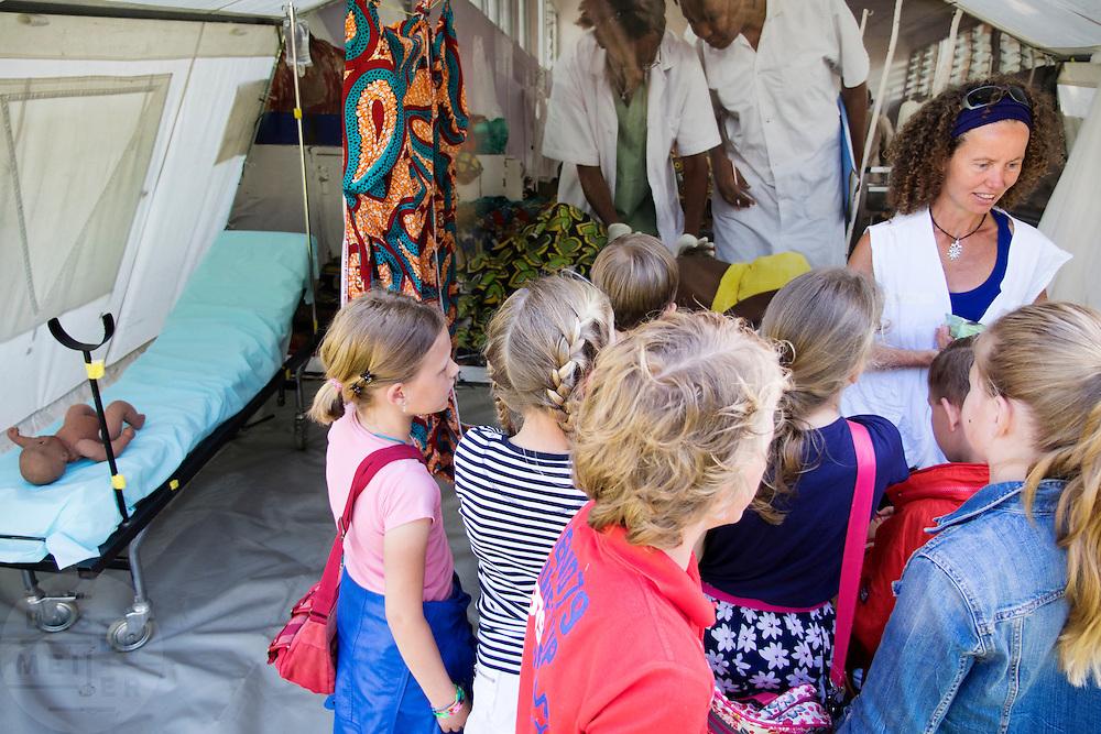 Een hulpverlener van Artsen Zonder Grenzen geeft scholieren uitleg over de moeder- en kinderzorg. In Utrecht heeft Artsen Zonder Grenzen een tentenkamp opgezet in het park Lepelenburg. Met het kamp wil de organisatie laten zien welk medische noodhulp het verricht in de noodhulpkampen in de wereld. Hulpverleners van AZG geven rondleidingen door  onder meer een (opblaasbaar) veldhospitaal, een voedingskliniek en een cholerakliniek.<br /> <br /> In Utrecht, MSF has set up a tent camp in the park Lepelenburg. In the camp, the organization wants to show what kind of emergency medical services they provide in the emergency camps in the world. MSF aid workers give tours including a (inflatable) field hospital, a nutrition clinic and a cholera clinic.