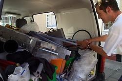Plumber unpacking tools from the back of his van north east England