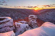 The sun sets over the snow laden Blackwater Canyon of West Virginia from the Lindy Point overlook on a chilly winter evening.