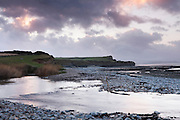 Kilve Pill, the outflow of the River Holford, as it flows across Kilve Beach after heavy rain on a January evening.
