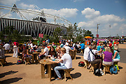 London, UK. Thursday 9th August 2012. London 2012 Olympic Games Park in Stratford. Food / eating area where people have picnic benches to rest and eat on to the backdrop of the stadium.