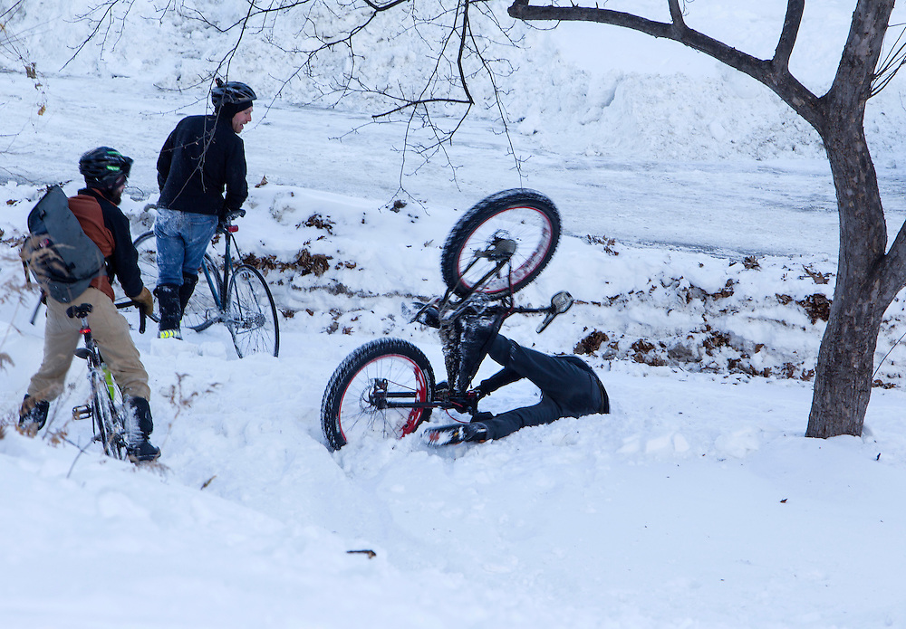 After riding down the snow-covered hill at Prospect Park's check-in point just for fun, race worker Rob Williams wipes out as competitors look on during Stupor Bowl 17 in Minneapolis February 1, 2014.