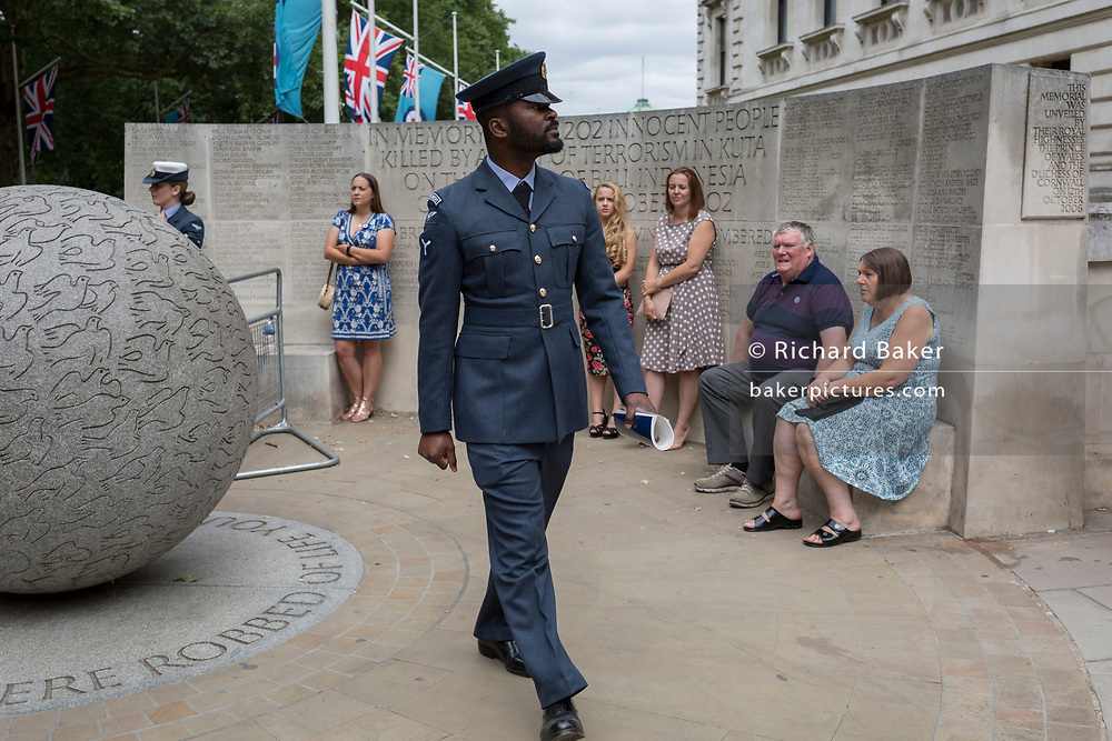 On the 100th anniversary of the Royal Air Force (RAF) and following a flypast of 100 aircraft formations representing Britain's air defence history which flew over central London, a servieman leaves Horseguards, passing the memorial to those killed in the 2002 Bali bombing, on 10th July 2018, in London, England.