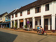 "13 MARCH 2016 - LUANG PRABANG, LAOS:  A Lao family on a motorcycle rides past a French colonial house that has been turned into a spa in Luang Prabang. Luang Prabang was named a UNESCO World Heritage Site in 1995. The move saved the city's colonial architecture but the explosion of mass tourism has taken a toll on the city's soul. According to one recent study, a small plot of land that sold for $8,000 three years ago now goes for $120,000. Many longtime residents are selling their homes and moving to small developments around the city. The old homes are then converted to guesthouses, restaurants and spas. The city is famous for the morning ""tak bat,"" or monks' morning alms rounds. Every morning hundreds of Buddhist monks come out before dawn and walk in a silent procession through the city accepting alms from residents. Now, most of the people presenting alms to the monks are tourists, since so many Lao people have moved outside of the city center. About 50,000 people are thought to live in the Luang Prabang area, the city received more than 530,000 tourists in 2014.   PHOTO BY JACK KURTZ"