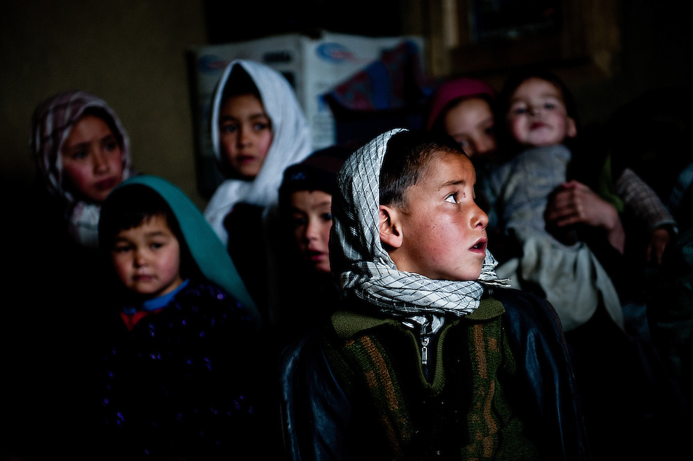 Moussa, 7, stands at the center of a gaggle of children in Abdul Ghani's main sitting room. Abdul Ghani, Jawkar's chief, hopes tourism development will bring money into Bamiyan's remote valleys so that they can build better schools and electricity infrastructure.