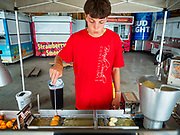 "26 JUNE 2020 - DES MOINES, IOWA: DRAKE HANSON fries mini donuts at Fair Food Friday in Des Moines. The 2020 Iowa State Fair, like many state fairs in the Midwest, has been cancelled this year because of the COVID-19 (Coronavirus) pandemic. The cancellation of the fair left many small vendors stranded with no income. Some of the fair food vendors in Iowa started ""Fair Food Fridays"" on a property a few miles south of the State Fairgrounds. People drive up and don't leave their cars while vendors bring them the usual midway fare; corndogs, fried tenderloin sandwiches, turkey legs, deep fried Oreos, lemonaide and smoothies. Fair Food Friday has been very successful. The vendors serve 450-500 people per Friday and during the lunch rush people wait in line in their cars 30 - 45 minutes to place an order.     PHOTO BY JACK KURTZ"