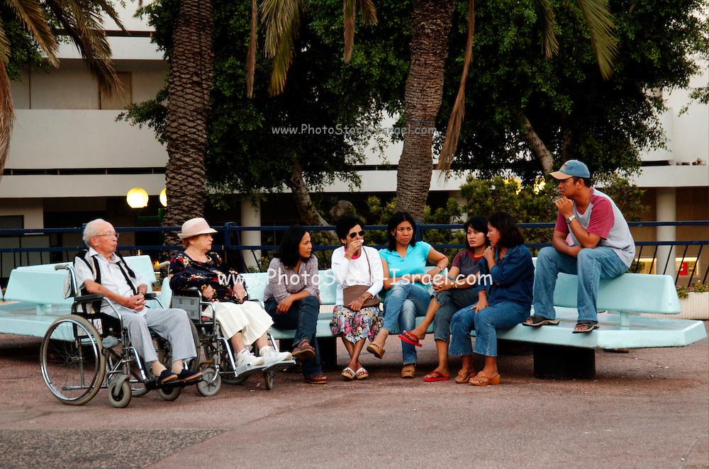 Israel, Tel Aviv Elderly handicapped people and their Philippino servants meet at Dizengoff circle in centre Tel Aviv