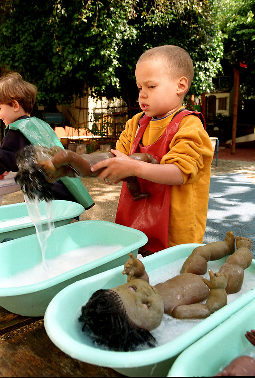 Two boys bathing dolls at open air nursery,