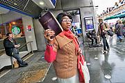 Engeland, London, 9-4-2019 Straatbeelden uit de wijk Brixton die een voor groot deel gekleurde, gemengde, bevolkingssamenstelling heeft .  Voor het metrostation proclameert een vrouw uit de bijbel . Foto: Flip Franssen