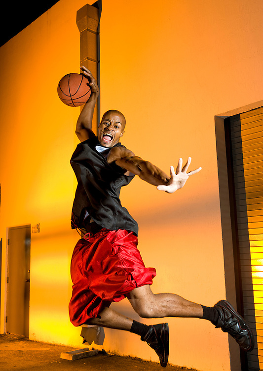 Basketball player jumping with ball in the street.