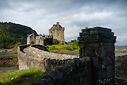 Eilean Donan offers one of the most iconic images of Scotland. It is situated on an island at the point where three great sea lochs meet, and surrounded by some majestic scenery.<br /> <br /> First inhabited around the 6th century, the first fortified castle was built in the mid 13th century and stood guard over the lands of Kintail. Since then, at least four different versions of the castle have been built and re-built as the feudal history of Scotland unfolded through the centuries.<br /> <br /> Partially destroyed in a Jacobite uprising in 1719, Eilean Donan lay in ruins for the best part of 200 years until Lieutenant Colonel John MacRae-Gilstrap bought the island in 1911 and proceeded to restore the castle to its former glory. After 20 years of toil and labour the castle was re-opened in 1932.<br /> <br /> This photograph is a colour version of the view of Eilean Donan Castle from the gatehouse. The photograph can be purchased as print, mounted print in frames, canvas or aluminum or as a digital file.