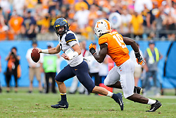 Sep 1, 2018; Charlotte, NC, USA; West Virginia Mountaineers quarterback Will Grier (7) runs out of the pocket while pressured by Tennessee Volunteers linebacker Darrell Taylor (19) during the second quarter at Bank of America Stadium. Mandatory Credit: Ben Queen-USA TODAY Sports