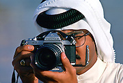 Man taking photograph using Asahi Pentax camera, Dubai