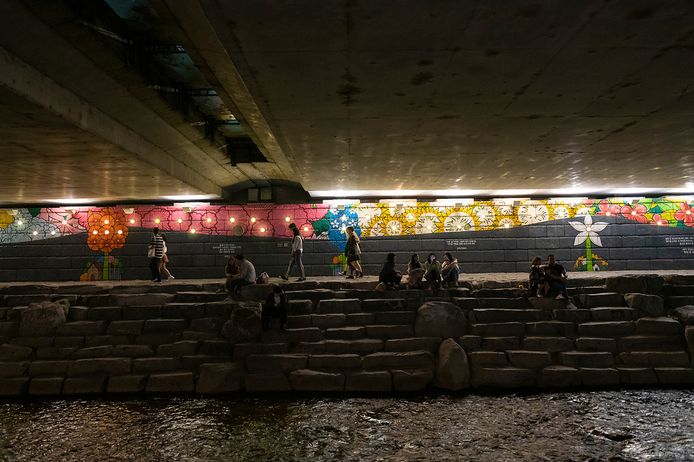 People sit and walk past a painted mural under a bridge at the Cheonggyecheon River, an 11 km long revitalized stream that runs through downtown Seoul. Korea.