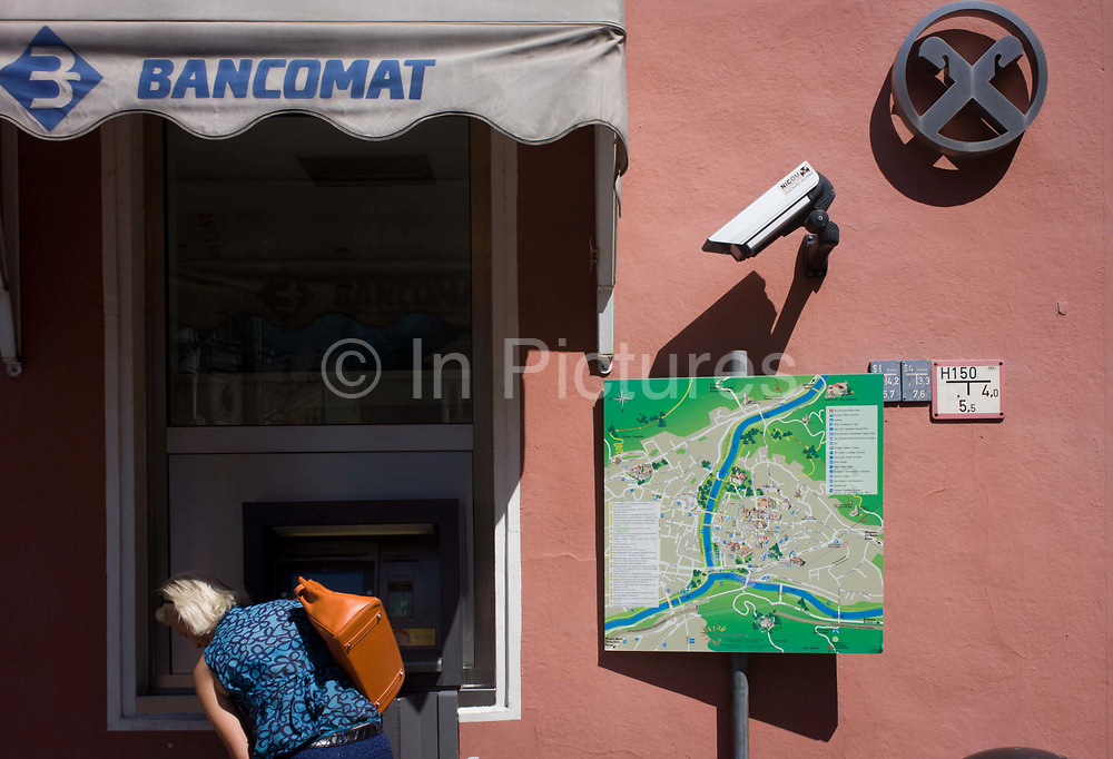 Under the gaze of CCTV, a customer uses a Bancomat cash dispenser in the northern Italian south Tyrolean city of Bozen-Bolzano. The woman leans over to see the screen in sunlight with the map of the city on the right. ATMs in South Tyrol are all called Bancomat and are wide-spread, even in smaller, rural villages. South Tyrol is one of the safest regions in Italy and in Europe and there are practically no violent crimes.