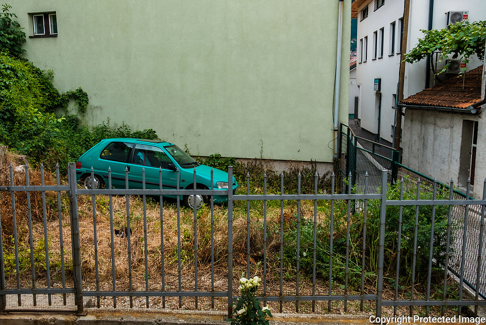 A car is parked in the fenced in garden of a home in downtown Sarajevo. A typical street scene in Sarajevo.