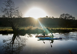 © Licensed to London News Pictures. 02/01/2017. Godalming, UK. Canoeists are reflected in the River Wey near Godalming at first light. A cold spell is expected to remain for most of the next week. Photo credit: Peter Macdiarmid/LNP