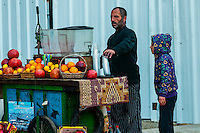 Man squeezing fresh pomegranate and orange juice at a sidewalk stall, Old City, Jerusalem, Israel.