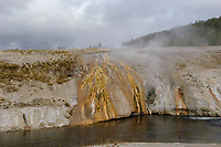 Boiling water bubbling up from a geyser and flowing into stream near Old Faithfull Geyser, Yellowstone National Park   Photo: Peter Llewellyn